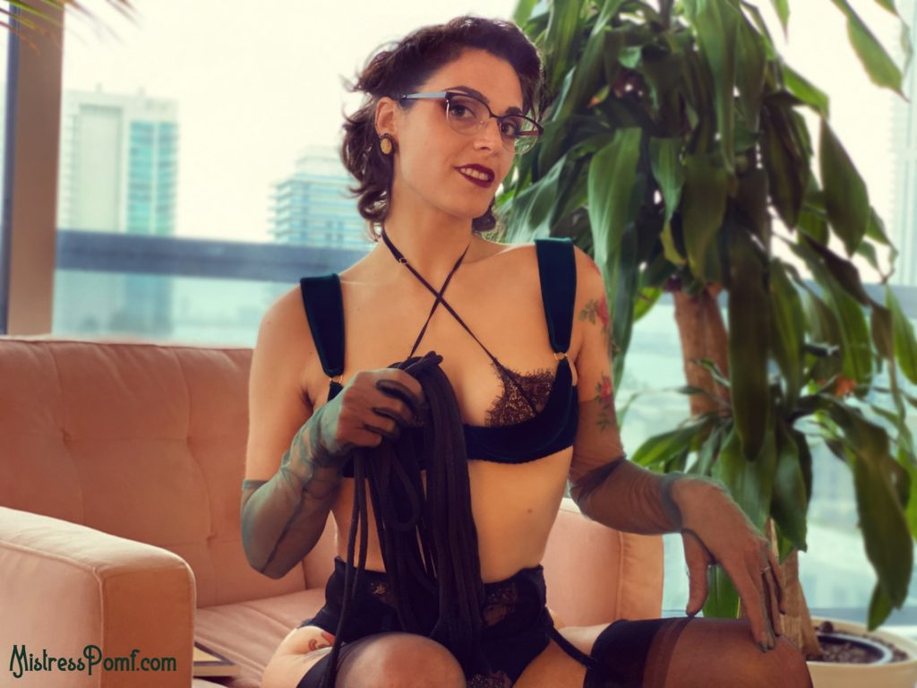 Dominatrix Mistress Pomf roleplays as The Librarian holding black rope symbolizing the bondage of her storyline.