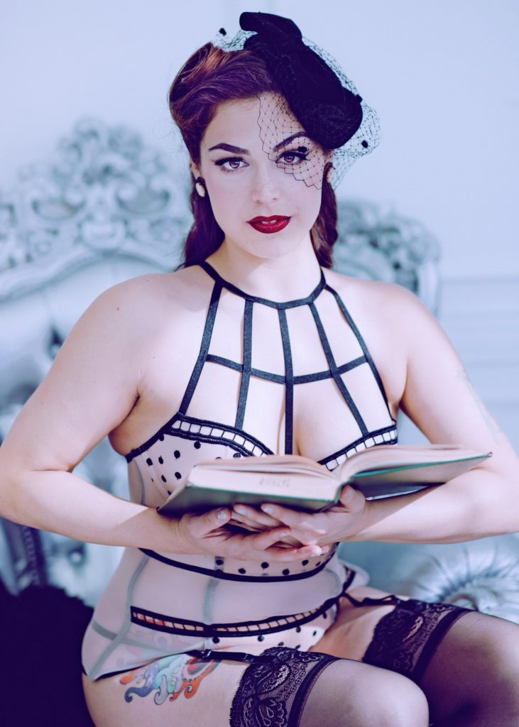 Role-play Dominatrix Mistress Pomf embodies the librarian as she holds an open book and looks at you with her stunning brown eyes.