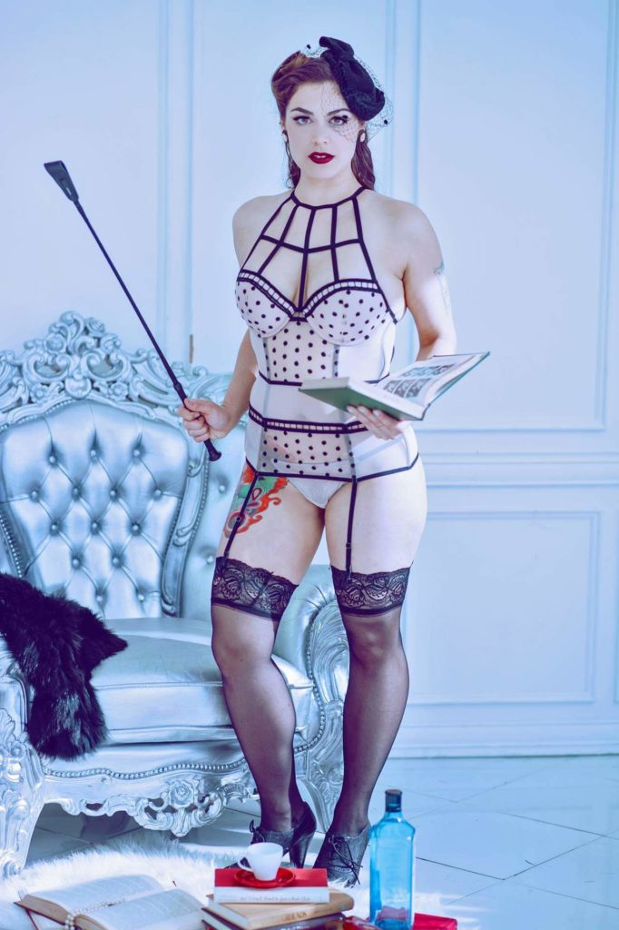 Florida Dominatrix Mistress Pomf looks sternly at you as she holds a riding crop in one hand and open book in another.